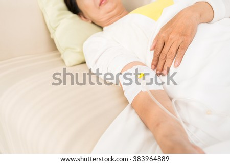 Elderly woman lying on the sofa with dropper: she is donating blood - stock photo