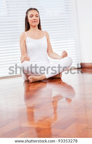 Elderly woman meditating relaxed in her living room - stock photo