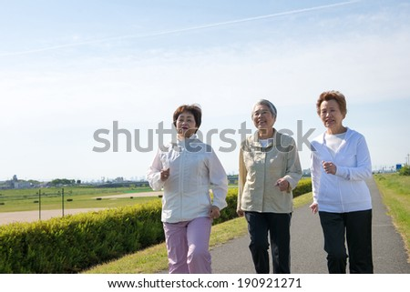 Elderly woman of Asian of three people walking down the road - stock photo