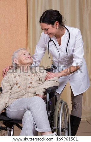 Elderly woman on a wheelchair with nurse