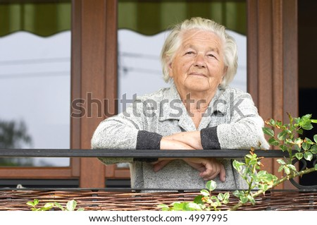 Elderly woman on the porch of her house. - stock photo