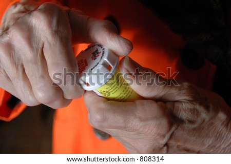 Elderly woman opens a pill bottle - stock photo