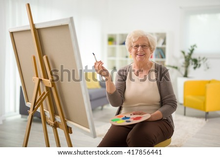 Elderly woman painting on a canvas seated on a chair at home - stock photo