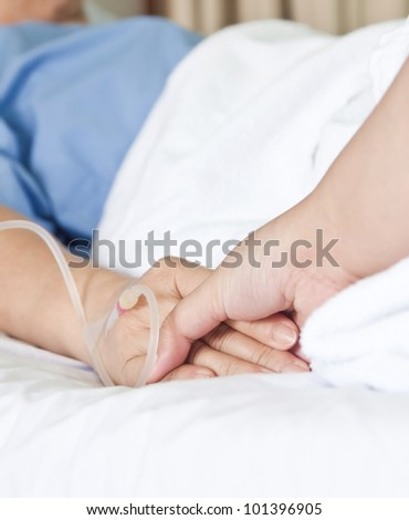 Elderly woman patient in bed with one hand being hold by daughter to be supportive