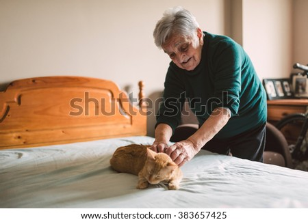 Elderly woman petting her cat on the bed at home