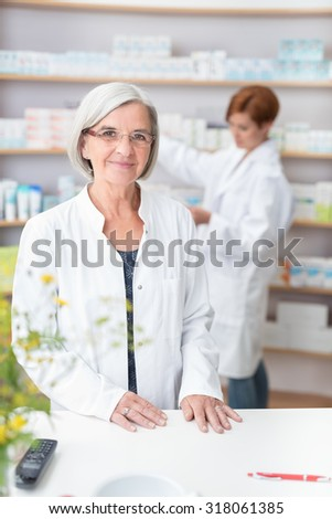 Elderly woman pharmacist in her pharmacy standing at the counter in her white lab coat as a female assistant checks stock on the shelves behind her