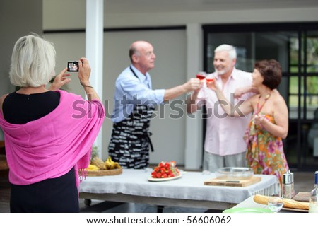 Elderly woman photographing a group of senior having a toast - stock photo