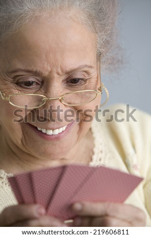 Elderly woman playing cards - stock photo