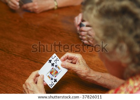 Elderly woman playing cards. Shallow depth of field. Focus on hands holding cards. Room for text. - stock photo