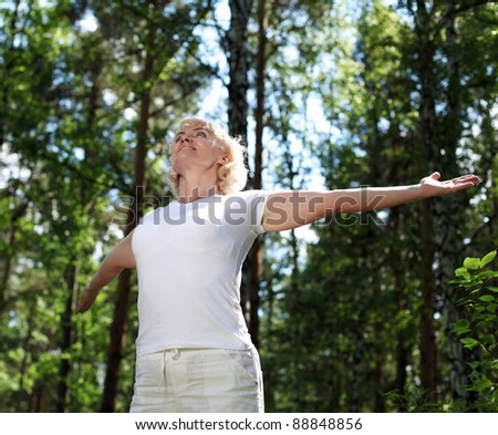 Elderly woman playing sports in the forest. - stock photo