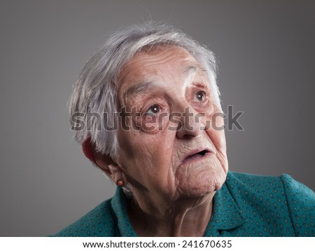Elderly woman portrait in a studio shot. Old woman is looking up.