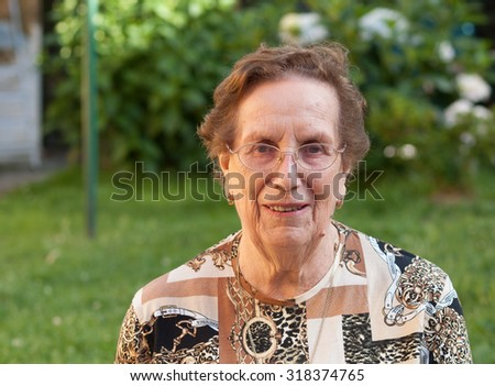 Elderly woman portrait outdoors. She is smiling. - stock photo