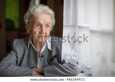 Elderly woman portrait, sitting in the house. - stock photo