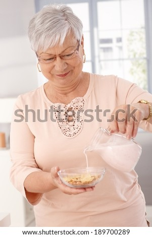 Elderly woman pouring milk over breakfast cereal, smiling. - stock photo