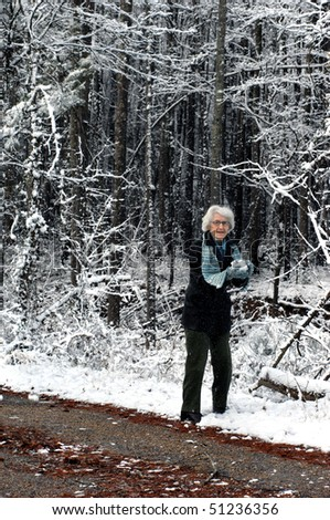 Elderly woman prepares a snowball to join in a snowball fight on a quiet country backroad.  Snow flakes shower upon her from the loaded trees overhead.
