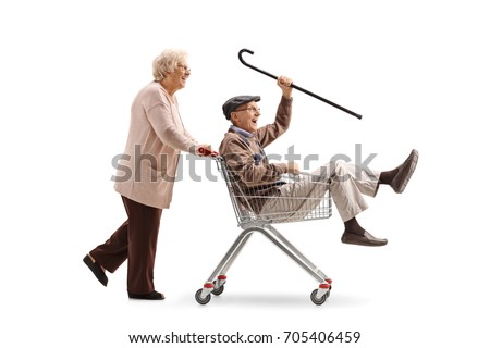 Elderly woman pushing a shopping cart with a senior riding inside it isolated on white background