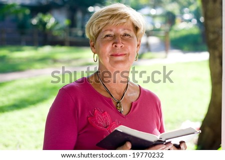 elderly woman reading a bible outdoors - stock photo