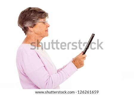 elderly woman reading book on tablet computer isolated on white - stock photo