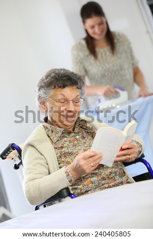 Elderly woman reading book while home helper irons laundry - stock photo