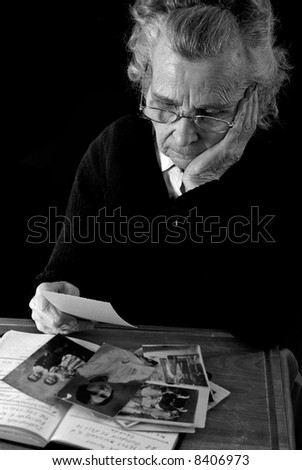 elderly woman reading old letters and looking at old photographs - stock photo