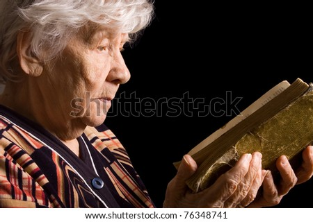 Elderly woman reads the book on black - stock photo
