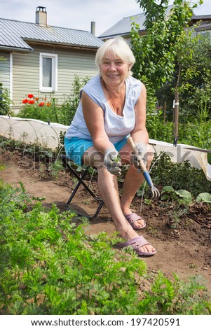 Elderly woman removes the weeds in the garden, sitting on a chair