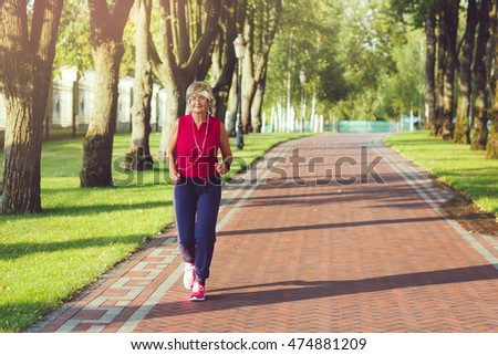 Elderly woman running with headphones and smartwatches in the park in evening sunset