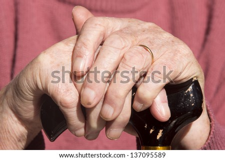 Elderly Woman's Hands/ an elderly widow rests her hands on her walking cane