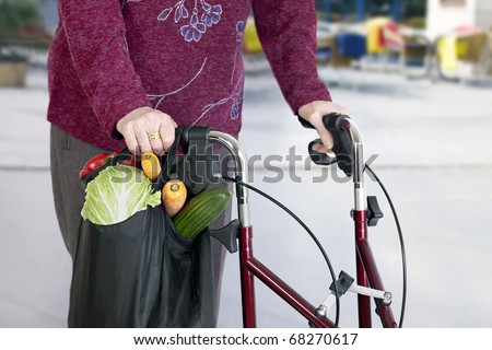 Elderly woman's hands on a walker taking a Shopping Bag with Vegetable - stock photo