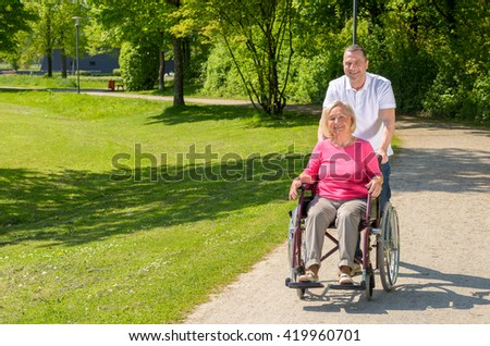 Elderly woman seated in wheel chair by standing husband on a park path on a bright summer afternoon - stock photo