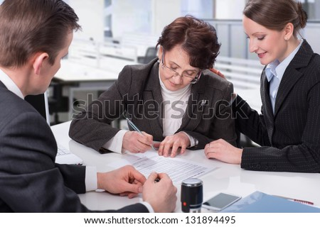 elderly woman signing a document at the office with managers - stock photo