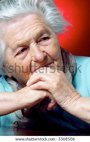Elderly woman sits at the table and contemplates - stock photo