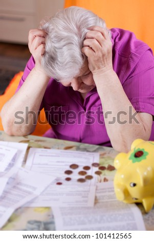 Elderly woman sits in front of papers and desperate - stock photo