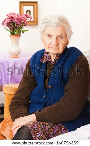 Elderly woman sits on the bed