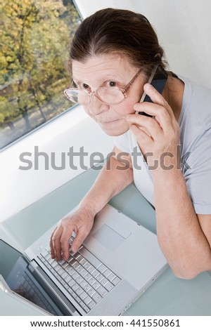 Elderly woman sitting at a laptop and talking on the phone. - stock photo