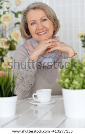 elderly woman sitting at a table with a cup of tea - stock photo