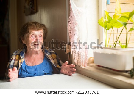 Elderly woman sitting at table and talk in his house. - stock photo