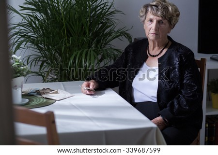 Elderly woman sitting at the table at home - stock photo