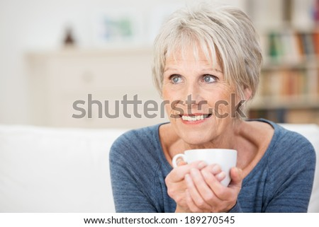 Elderly woman sitting daydreaming over a cup of aromatic coffee staring into the distance with a smile as she reminisces - stock photo