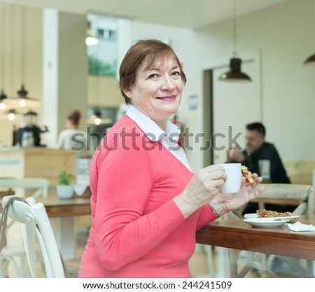 Elderly woman sitting in   cafe at   table.  - stock photo