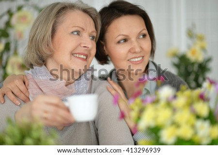 elderly woman sitting in flowers with her daughter and drinking tea - stock photo