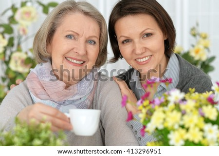 elderly woman sitting in flowers with her daughter and drinking tea