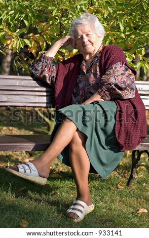 elderly woman sitting on a bench in the park/garden.