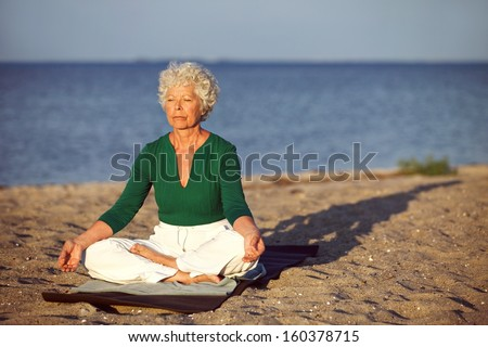 Elderly woman sitting on exercise mat doing meditation in lotus pose on the beach. Old woman doing relaxation exercise on the seashore. Meditation, yoga and relaxation concept - stock photo