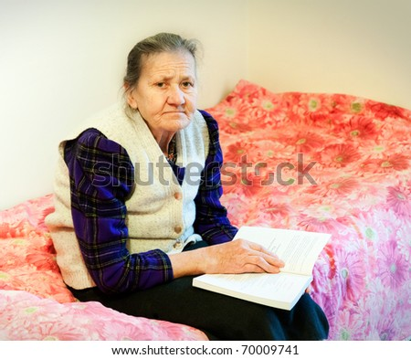 Elderly woman sitting on her bed with the bible in the hands - stock photo