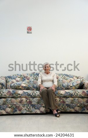 Elderly woman sitting on sofa in white room. - stock photo