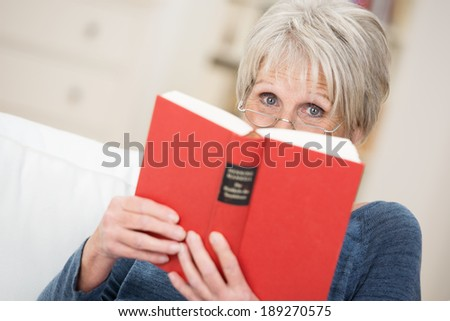 Elderly woman sitting on the sofa reading a book at home peering over the top in her reading glasses at the camera - stock photo