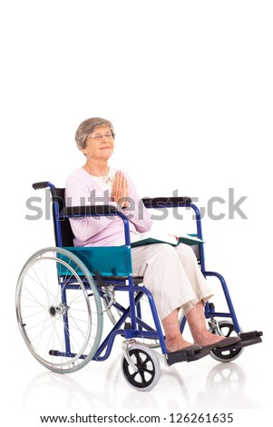 elderly woman sitting on wheelchair and praying isolated on white - stock photo