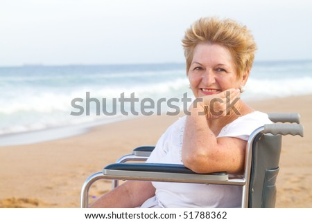 elderly woman sitting on wheelchair on beach - stock photo