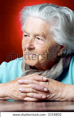 Elderly woman sitting with her hands clasped and looking away - stock photo